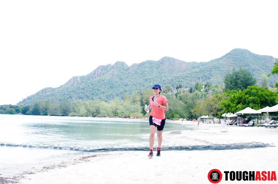 A jubilant Alicia running on Pantai Kok's soft sandy beach with Mat Chinchang mountain as a stunning backdrop into the finish line.
